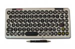 Large rectangular keyboard with black keys on beige background with pen in front.