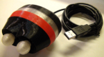 Oval-shaped device with two white knobs on one end, a red band around the center, and connected to a USB cable.