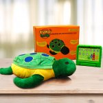 Photograph of plush turtle toy on a table with an orange box and a small green tablet device.