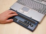 A blue braille keyboard attached to the bottom of a laptop.