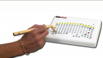 A person holding a bent wooden stylus/ stick to press a key on a white rectangular keyboard. The keys have a slight arc-shape layout.