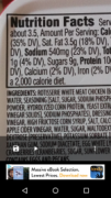 Nutrition facts and ingredients of a food product magnified on a phone screen.