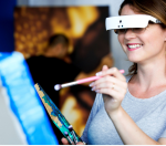 A woman painting while wearing glasses with a white panel across the lenses.