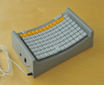 A corded, elevated keyboard with keys arranged within a tight, rectangular area along a downwardly curved surface. They keyboard is grey in color.