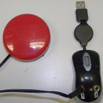 A black mini SwitchPort which appears like a computer mouse attached to USB cable. It has two input ports; a red switch is attached via left input port.