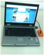 A silver, open laptop next to a bright orange rectangular switch connected via a black cord.