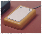 A small, wired, rectangular device the size of a computer mouse with a wooden base and a metal switch plate.