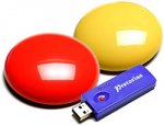 Two round flat wireless switches the size of a billiard ball with a USB drive.