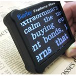Small, handheld device with large screen displaying enlarged text when positioned over a newspaper.