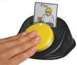 A yellow button positioned at an angle on a black, wedge-shaped device with a slot to hold a paper card with a word and an image.