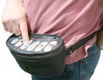 Black pouch strapped around the waist of a person with a white flat surface and six buttons with icons.