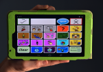 A sample AAC communication grid created with The Open Voice Factory is displayed on a tablet device.