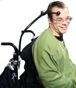 Person in wheelchair with switch attached to chair and head.