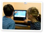 Two children interacting with Azahar on tablet.