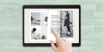 A hand turns the page of a digital magazine on a touchscreen e-reader device.