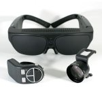 Large, black set of goggles worn over the head. A small camera lens and another component sit in front.