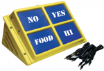 """A medium-sized, yellow, and rectangular device that features four blue squares with writing. The squares read """"no,"""" """"yes,"""" """"food,"""" and """"hi."""" The device has a built-in kickstand. A black cord is shown next to the device."""