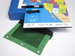 Shown is what's included: large printout of United States map, folded atop the box, with states in different colors, a green plastic pouch on the lower left and a special pen and cord sitting on the map.