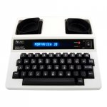 A TTY device resembling an electric typewriter. The keys and display panel are black, while the device body is off-white.