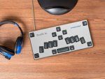 A silver Braille keyboard with black keys placed on top of a wooden surface next to a pair of blue headphones.