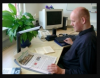 A man is sitting at a desk with his left hand on the bottom edge of a paper and his right on a keyboard that is sitting on top of a braille display. The paper is under a camera for OCR.